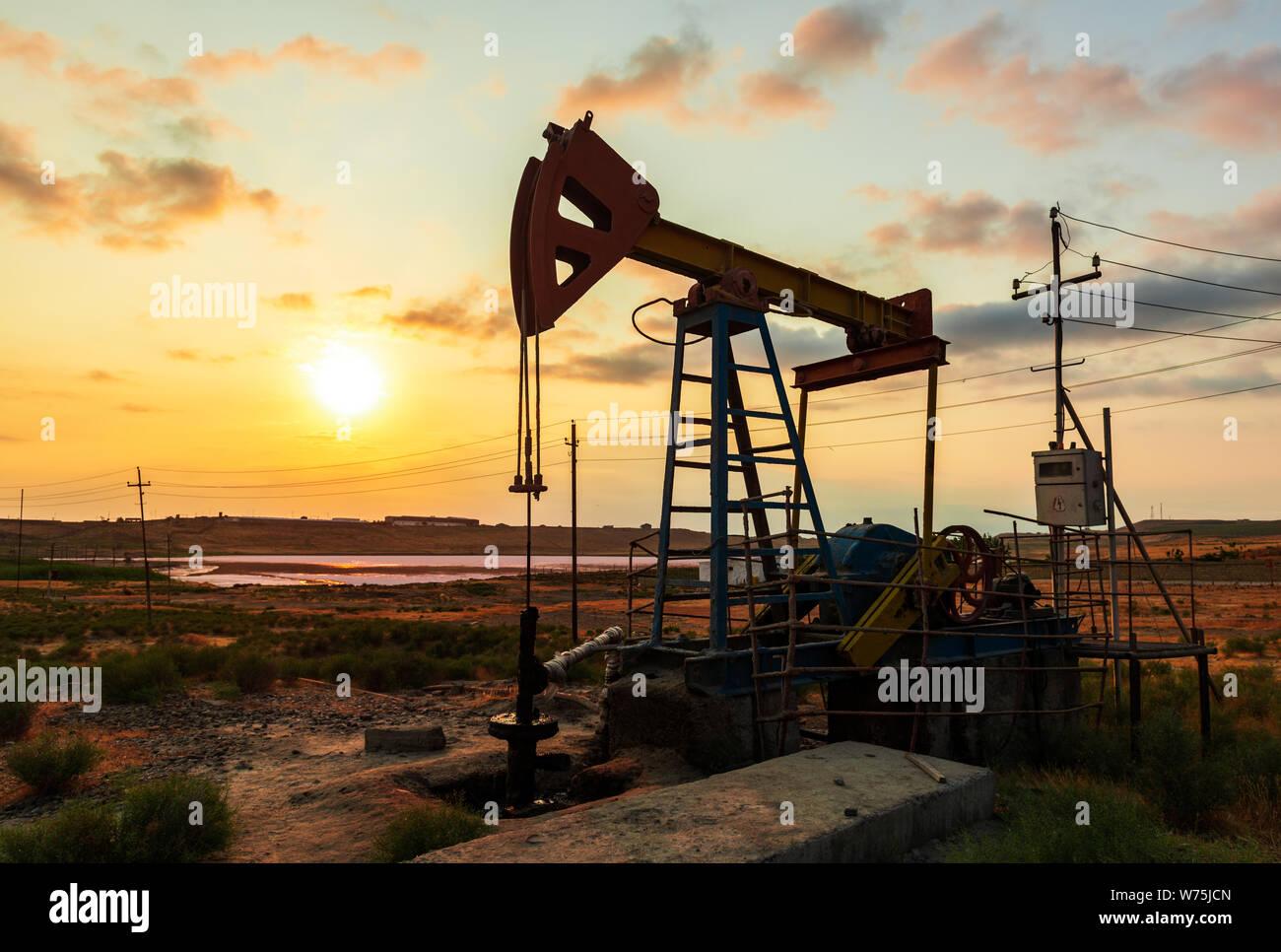 Oil Rig bomba contra un colorido atardecer cielo Foto de stock
