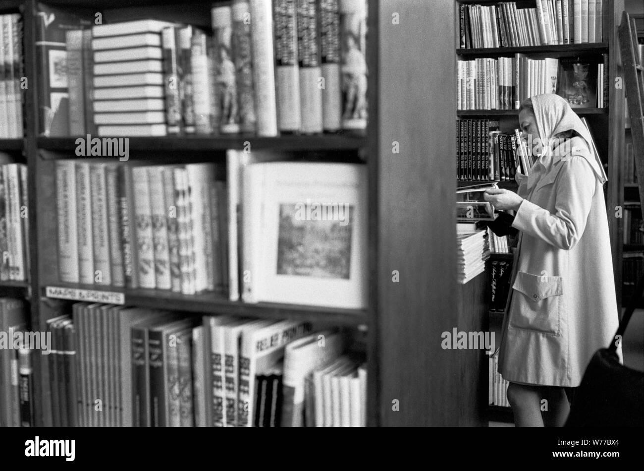 1970 Book Shop mujer tomar una decisión comercial navegación, compra decidir sobre qué libro comprar. 70S UK HOMER SYKES Foto de stock