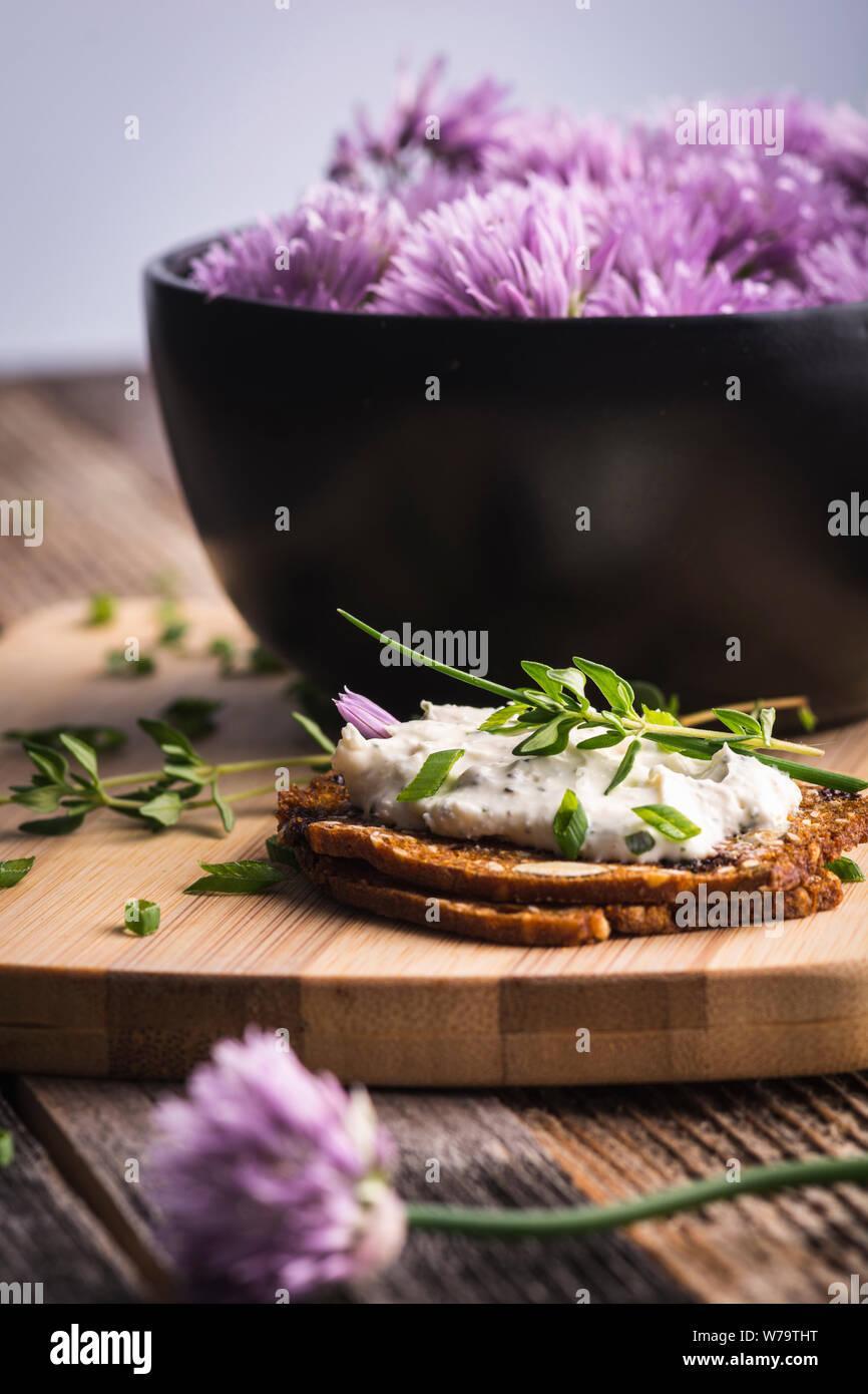 Una deliciosa crema de cebollino de ajo y queso para untar sobre galletas herbed junto a un tazón de flores púrpura de cebolleta. Foto de stock