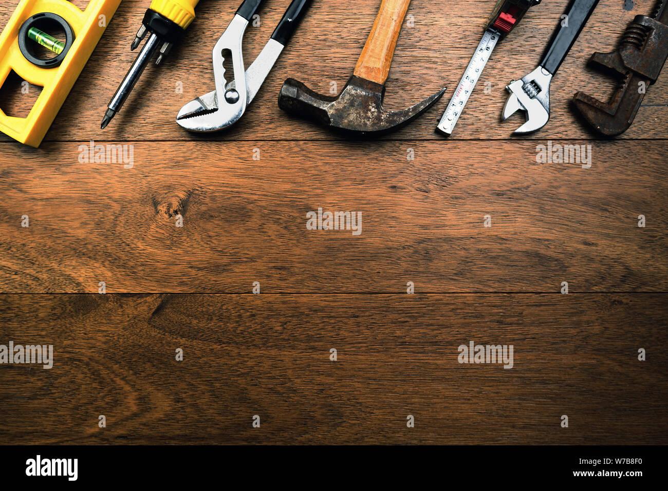 Sucio rusty artesanos herramientas como la escala de agua, alicates, destornillador, Martillo y cinta de medir sobre tablones de madera con espacio para la escritura Foto de stock