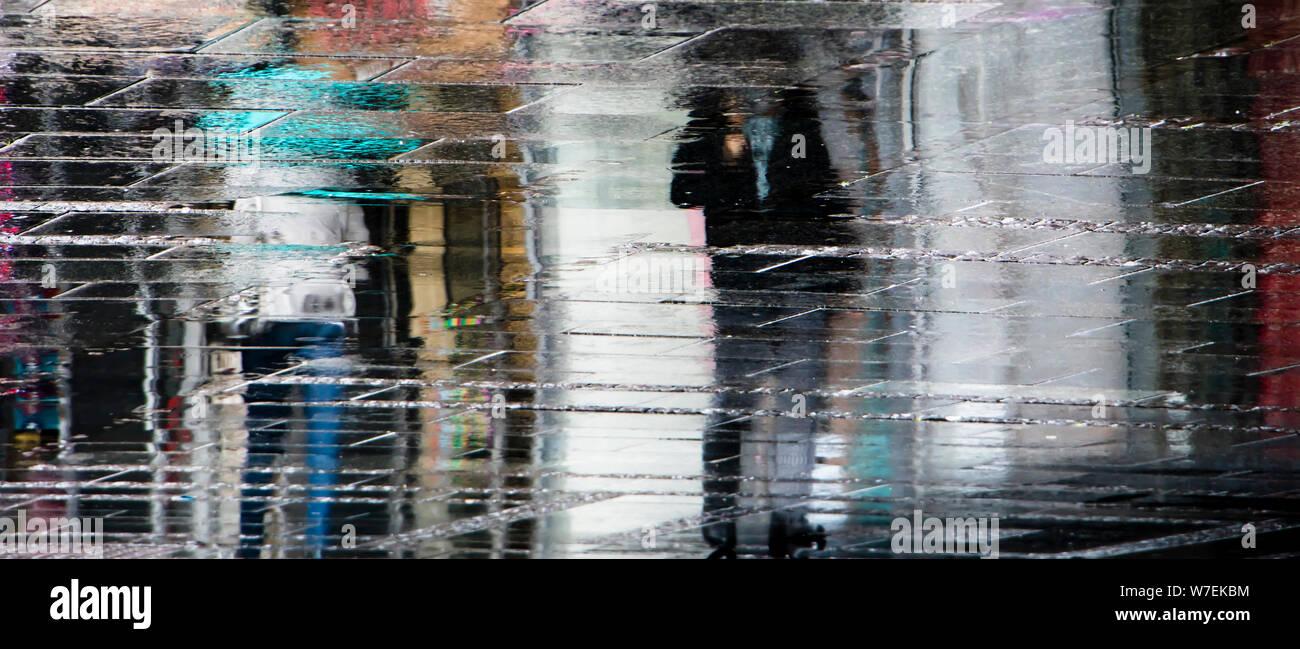Reflexión borrosa sombra siluetas de gente caminando bajo el paraguas en una lluviosa ciudad peatonal calle húmeda, en un charco Foto de stock