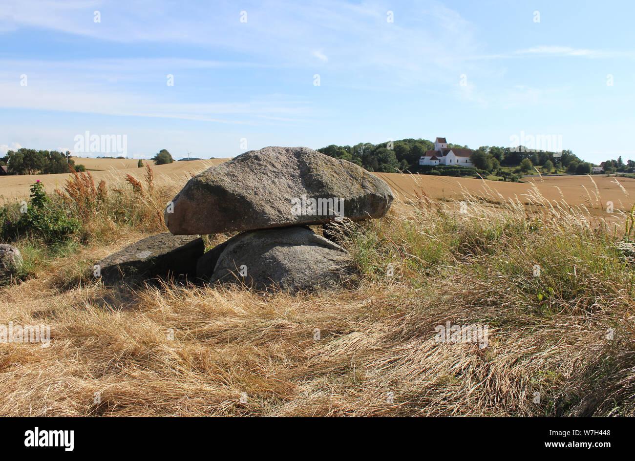 Dolmen de Kong humilla grave e Iglesia humilde en el fondo con escenas rurales circundantes. Langeland, Dinamarca. Foto de stock