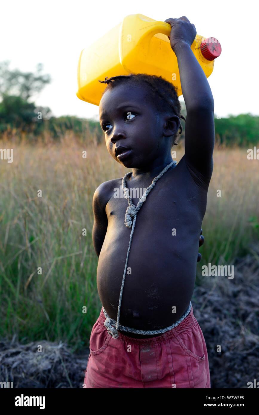 Niño llevar una botella de agua por encima de la cabeza, aldea de Eticoga, Isla de Orango, Guinea-Bissau, diciembre de 2013. Foto de stock