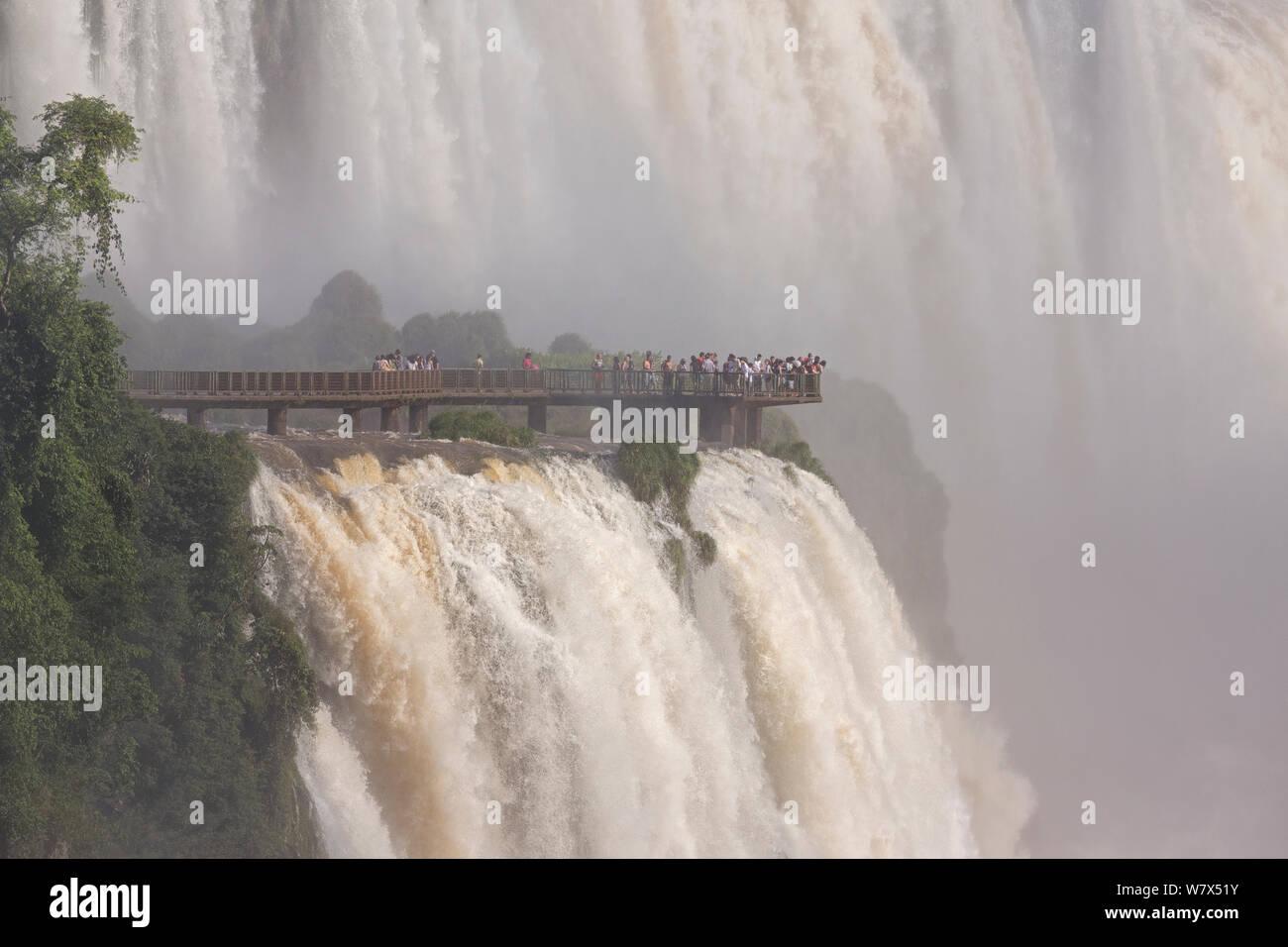 Las Cataratas de Iguazú y los turistas en plataforma de visualización, las Cataratas del Iguazú, Parque Nacional de Iguazú, Brasil, en enero de 2014. Foto de stock