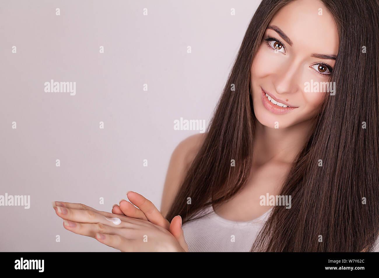 Aplicar crema cosmética. Una joven y bella mujer de aplicar la crema hidratante facial. Scine cuidado de la cara y las manos Foto de stock