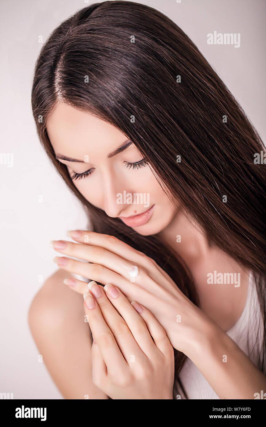 Tratamiento facial. Mujer en el Salón de belleza. Aplicar crema cosmética. Una joven y bella mujer de aplicar la crema hidratante facial. Scine cuidado de la cara y las manos Foto de stock