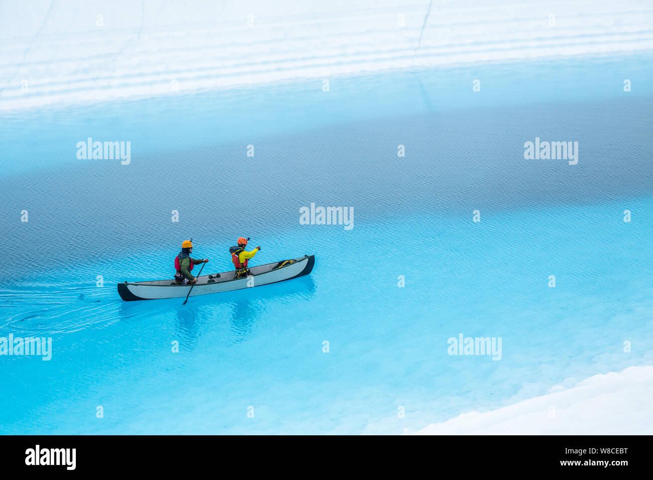 Dos hombres remar una canoa inflable en la parte superior de una piscina azul en el Glaciar Matanuska en el desierto de Alaska. El lago azul es un lago supraglacial, Foto de stock