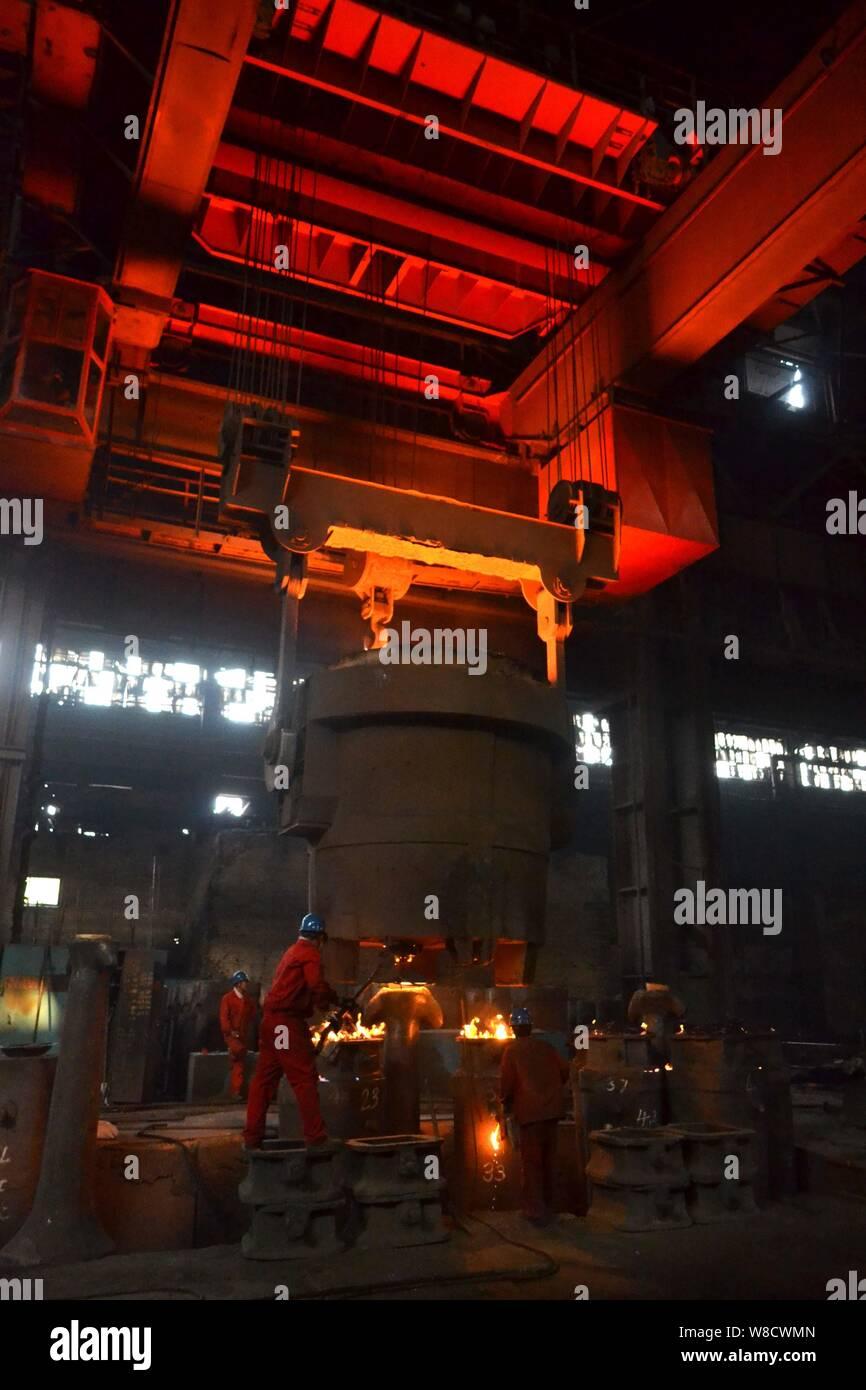 --FILE--Los trabajadores chinos encuesta la producción de acero alrededor de un horno que contiene el acero fundido en una planta de acero especial de Dongbei Group Co., Ltd. Foto de stock