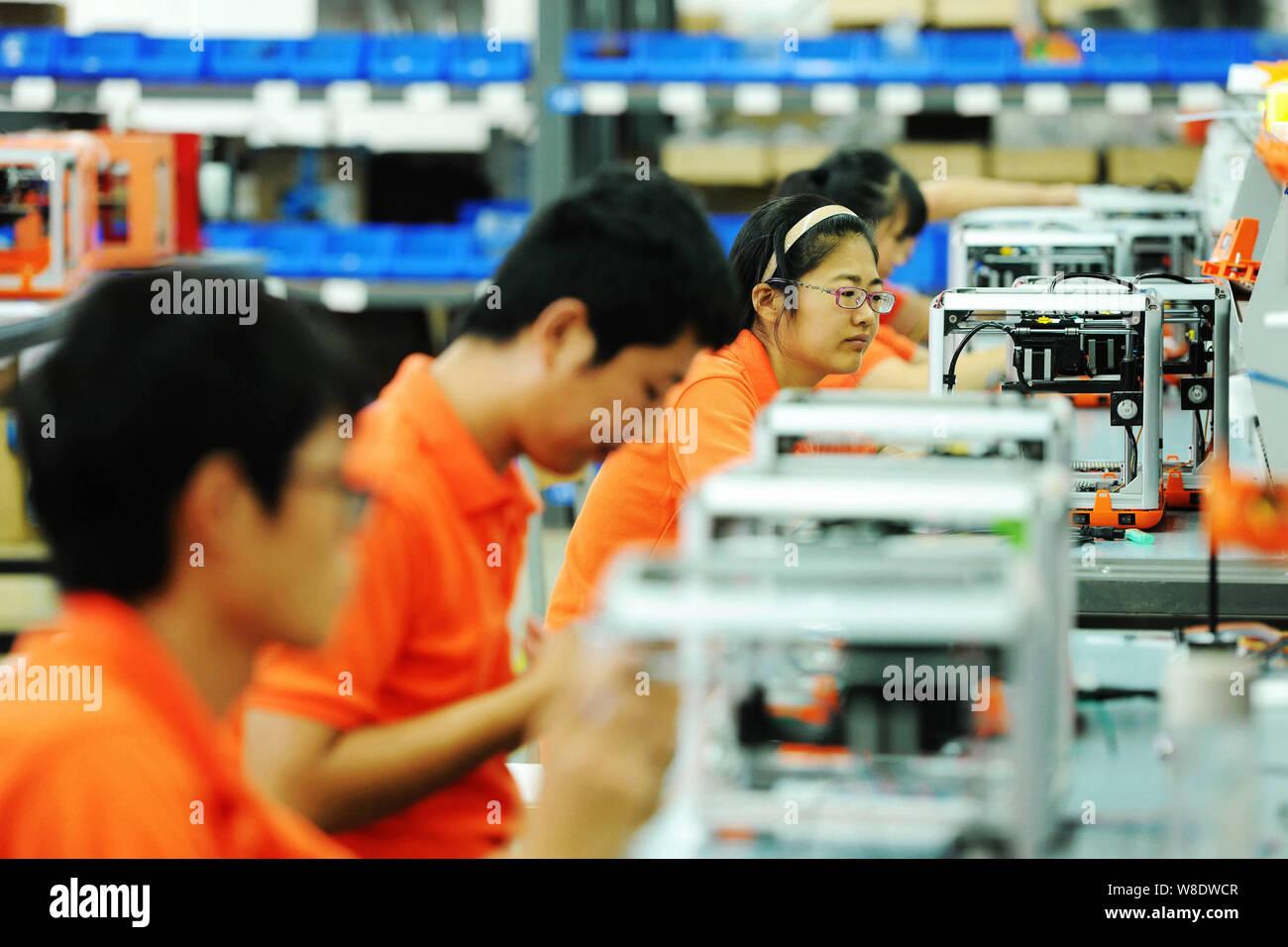 --FILE--Los trabajadores chinos armado con las impresoras 3D en una fábrica en la ciudad de Qingdao, Provincia de Shandong, en el este de China, el 1 de septiembre de 2015. Una semana después de que China dijo Foto de stock
