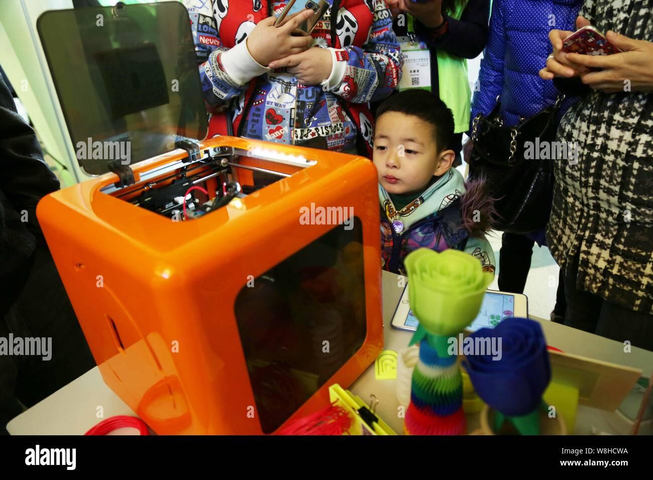 --FILE -- un joven visitante busca una impresora 3D durante una exposición en Shanghai, China, 27 de noviembre de 2015. Envío de las impresoras 3D de la marca china Foto de stock