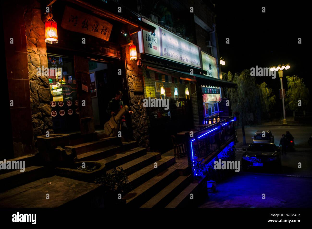 Ancianos mujer chino Cai Yuanxiu llevando su guitarra deja un pub en Yunyang County, Chongqing, China, el 11 de enero de 2016. Mujer chino Cai Yuanxiu i Foto de stock