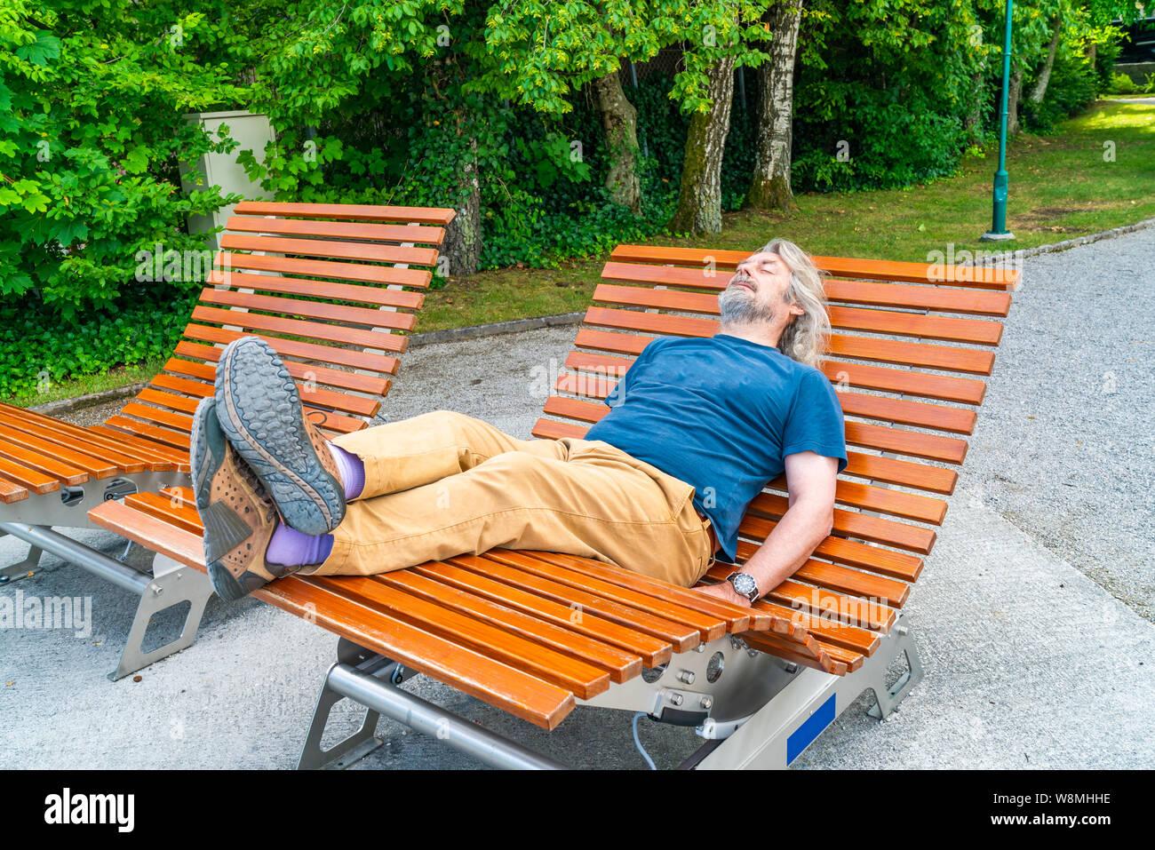 Un varón de mediana edad relajándose en una silla mecedora de madera en el parque público. Foto de stock