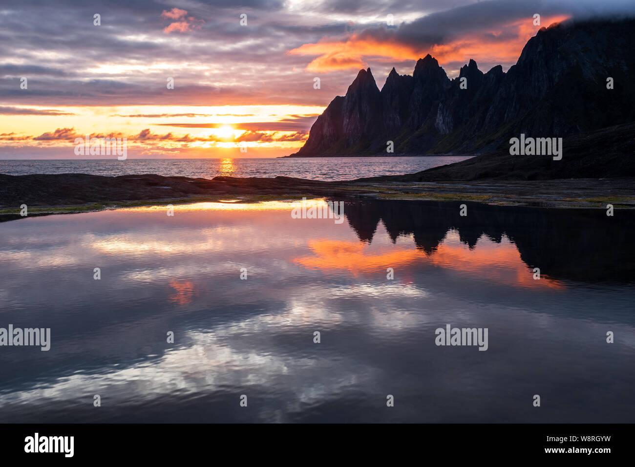 Reflejo en un rockpool de impresionante Cordillera Oksen en muy colorido atardecer, Tungeneset, Senja, Noruega Foto de stock