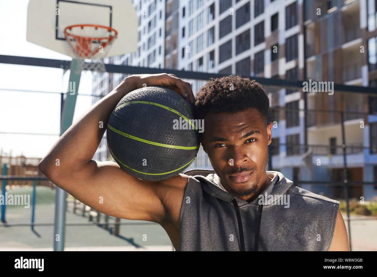 Retrato de apuesto hombre afroamericano la celebración de pelota de baloncesto mirando a la cámara mientras posan en la cancha de deportes al aire libre, espacio de copia Foto de stock
