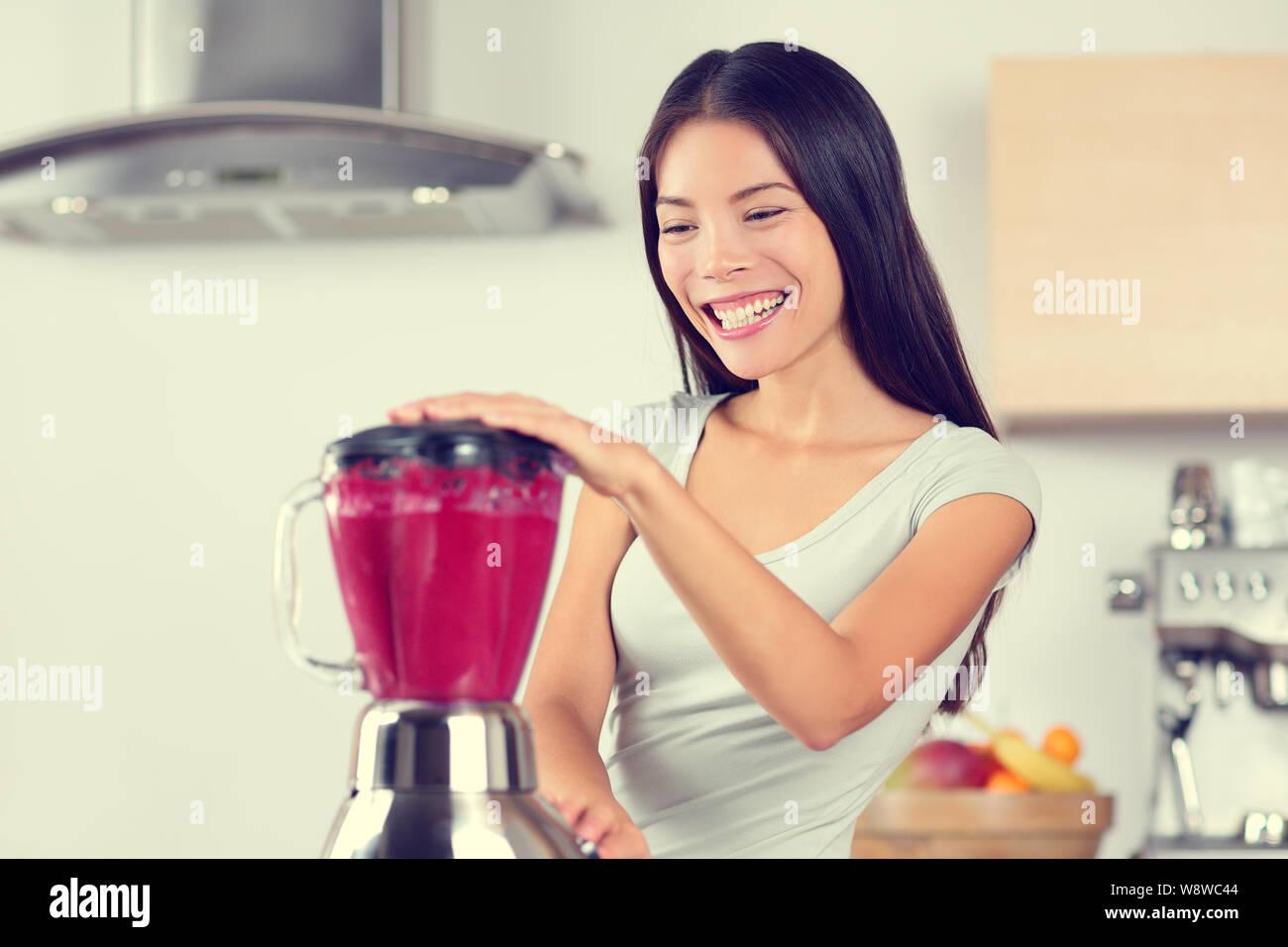 Mujer haciendo batidos batido con la batidora. Comer sano