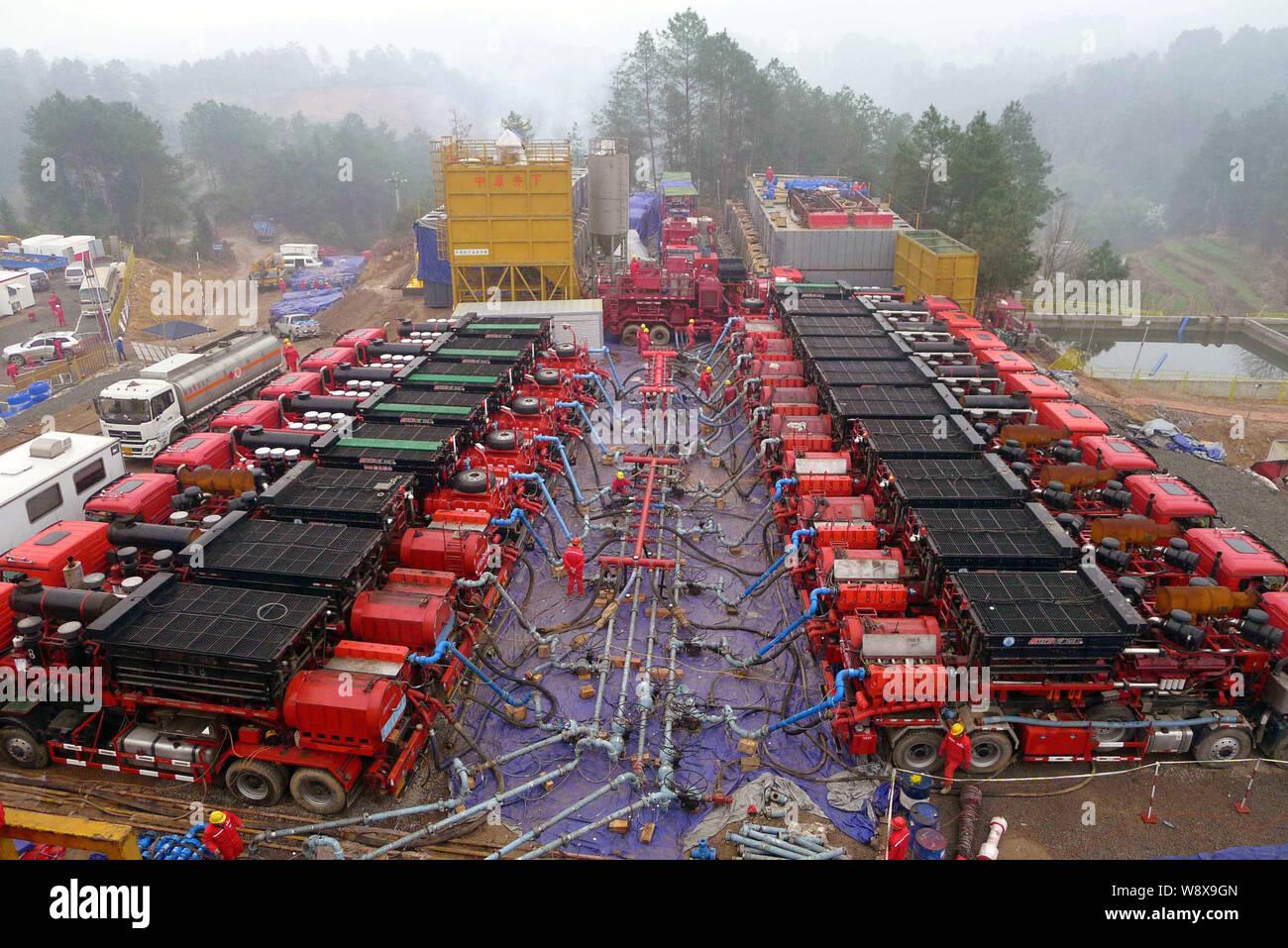 --FILE--Los trabajadores chinos supervisar los tubos conectados a los vehículos durante una operación de fracturación hidráulica shale gas en un pozo de la Sinopec Fuling Shal Foto de stock