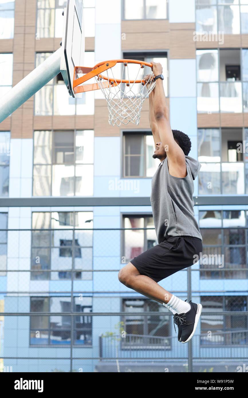 Vista lateral de disparo de acción del jugador de baloncesto africano saltando al aro, mientras que la capacitación en corte, copie el espacio exterior Foto de stock