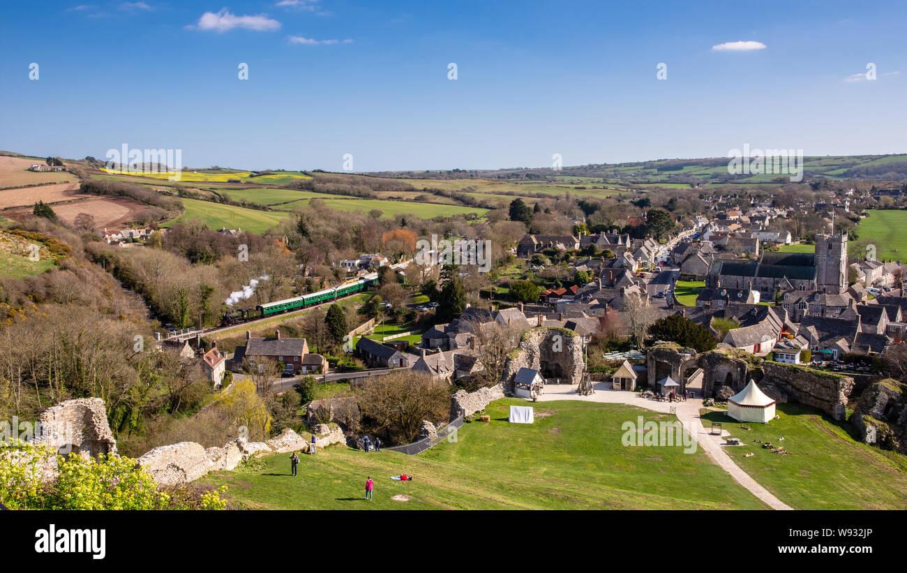 El castillo Corfe, Inglaterra, Reino Unido - 27 de marzo de 2019: un tren de vapor pasa el castillo Corfe village en Swanage Railway en Dorset. Foto de stock