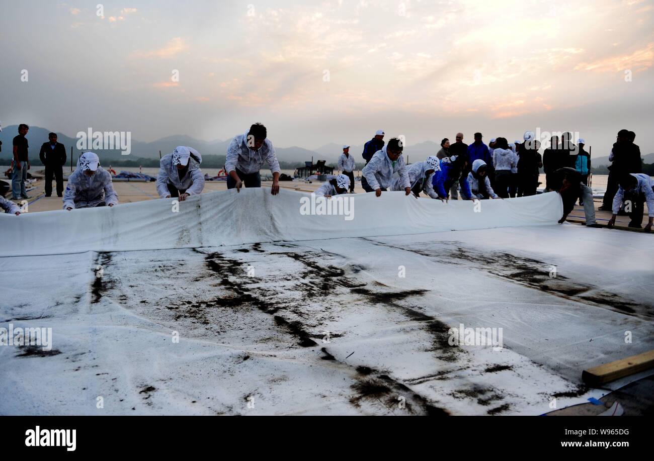 Los funcionarios enrollar un trozo de seda, en la que el artista contemporáneo chino Cai Guoqiang pintados de primavera con pólvora en una plataforma en el lago Oeste i Foto de stock