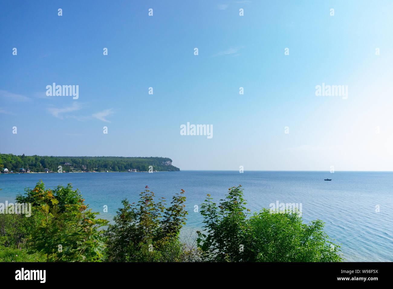 Barco flotando cerca de la cabeza del león, la Península de Bruce en Ontario con plantas y acantilados en el fondo Foto de stock