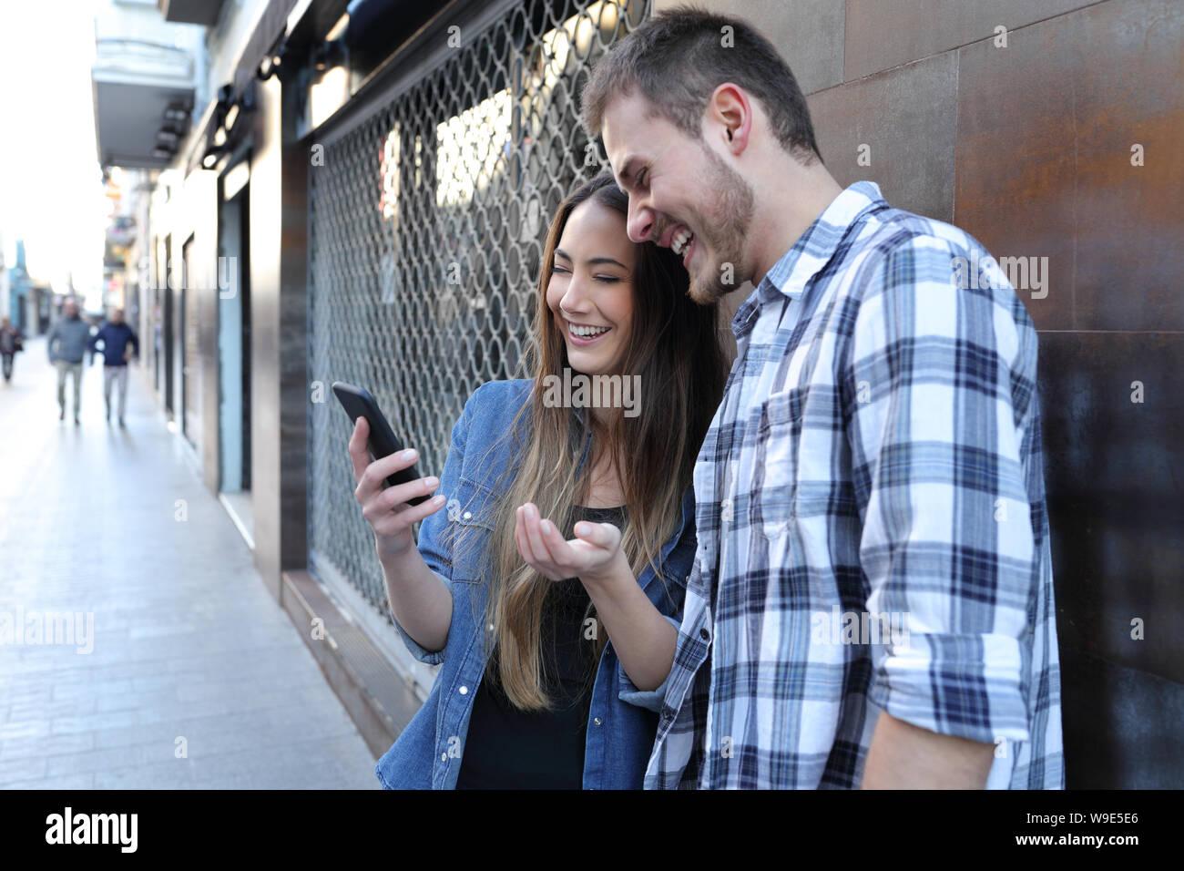 Feliz pareja sorprendente comprobar el contenido del teléfono inteligente de pie en la calle Foto de stock