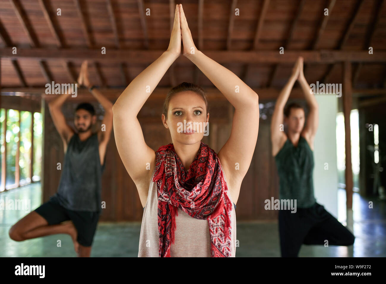 Hermosa hembra profesor dando clase de yoga a dos hombres de raza mixta en las esteras del yoga en templo tradicional en Bali Indonesia Foto de stock