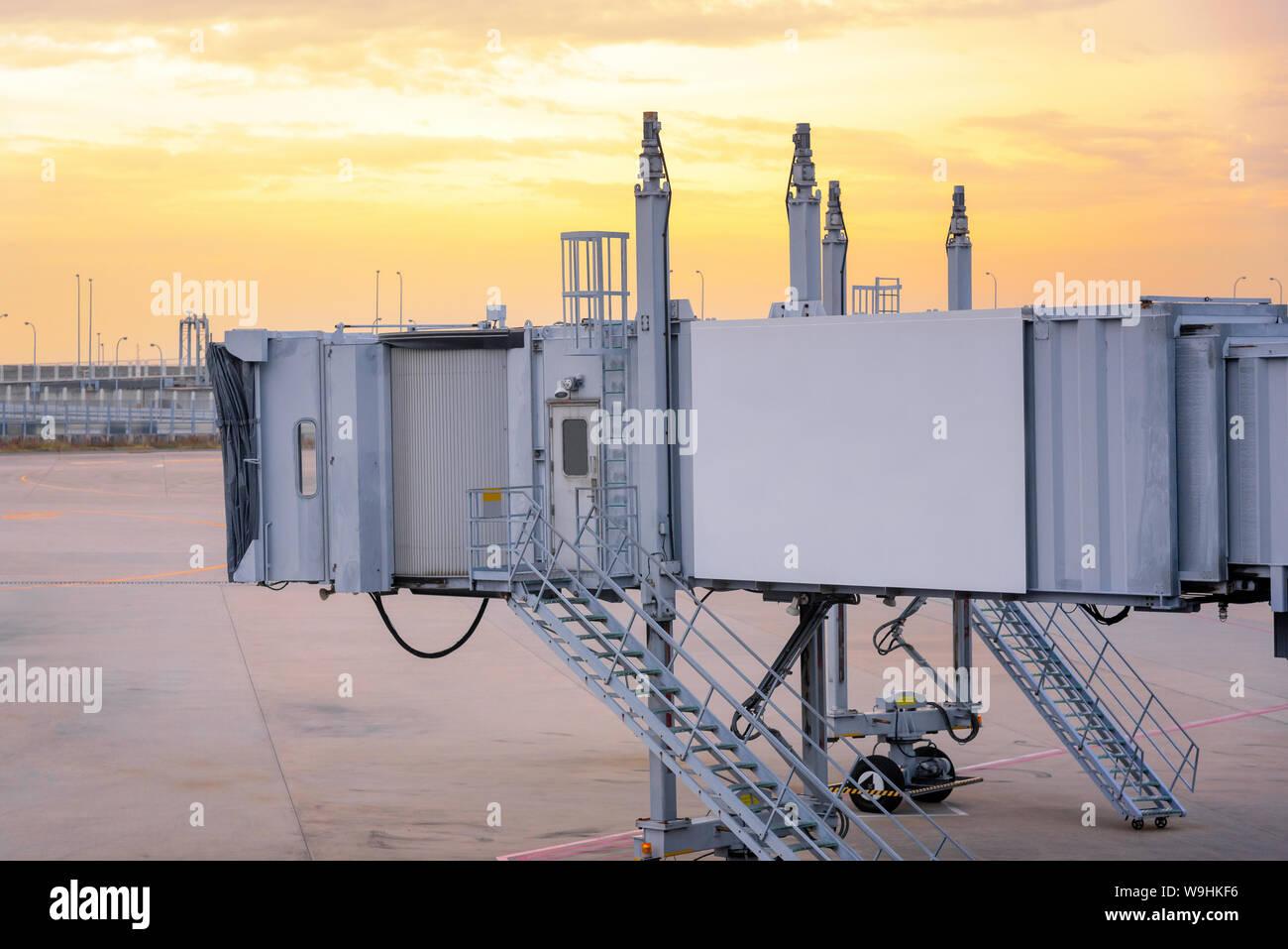 Puente de embarque de pasajeros esperando un avión para llegar a la terminal del aeropuerto internacional de la compuerta. Foto de stock