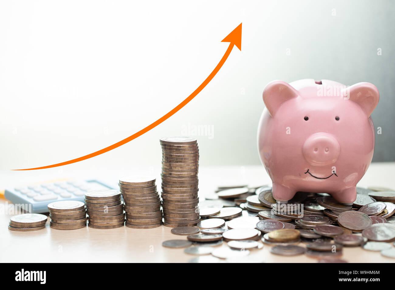 Ahorro de dinero concepto.business ricos ingresos muestran como pila dinero coin creciente con flecha hucha sonrisa con monedas montón. Foto de stock