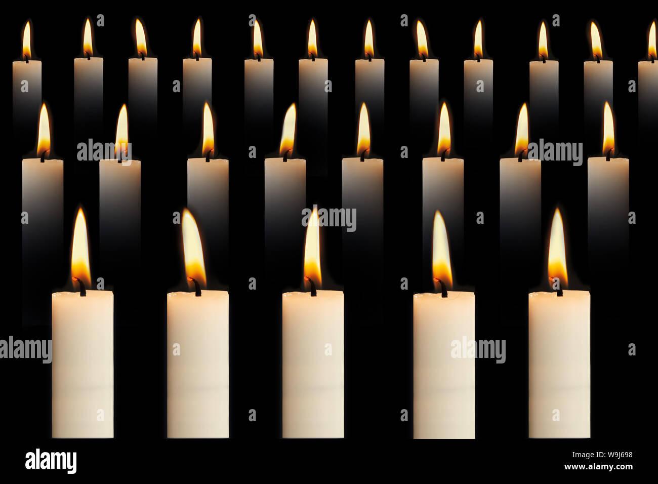 Muchas velas encendidas en filas sobre fondo negro. La fe, la religión, el honor o el concepto de espiritualidad. - Imagen Foto de stock