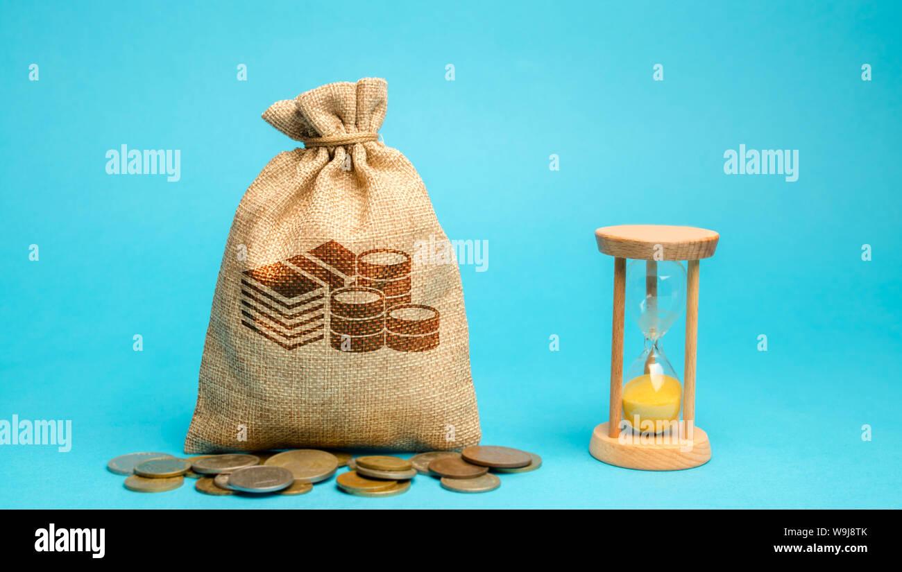 Bolsa de dinero con monedas y un reloj / reloj de arena. La gestión del tiempo y la distribución. Concepto de ahorro de dinero. La planificación del trabajo. La estrategia empresarial y investme Foto de stock