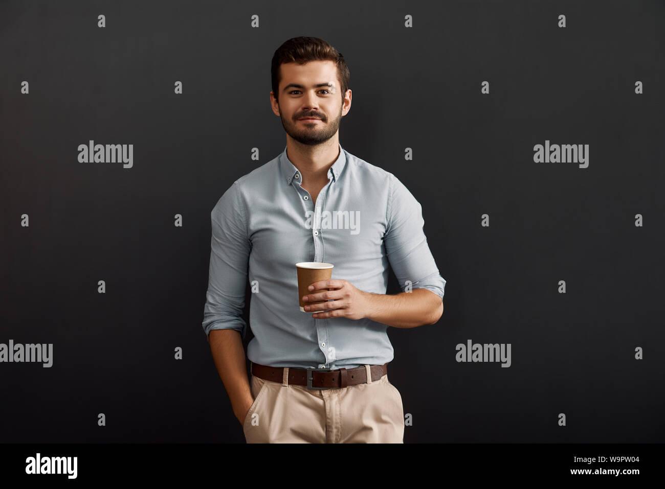 Sólo un minuto para relajarse. Joven barbudo alegre hombre sujetando una taza de café caliente y mirando a la cámara con una sonrisa mientras está de pie contra un fondo oscuro. Pausa para el café. Foto de Estudio Foto de stock