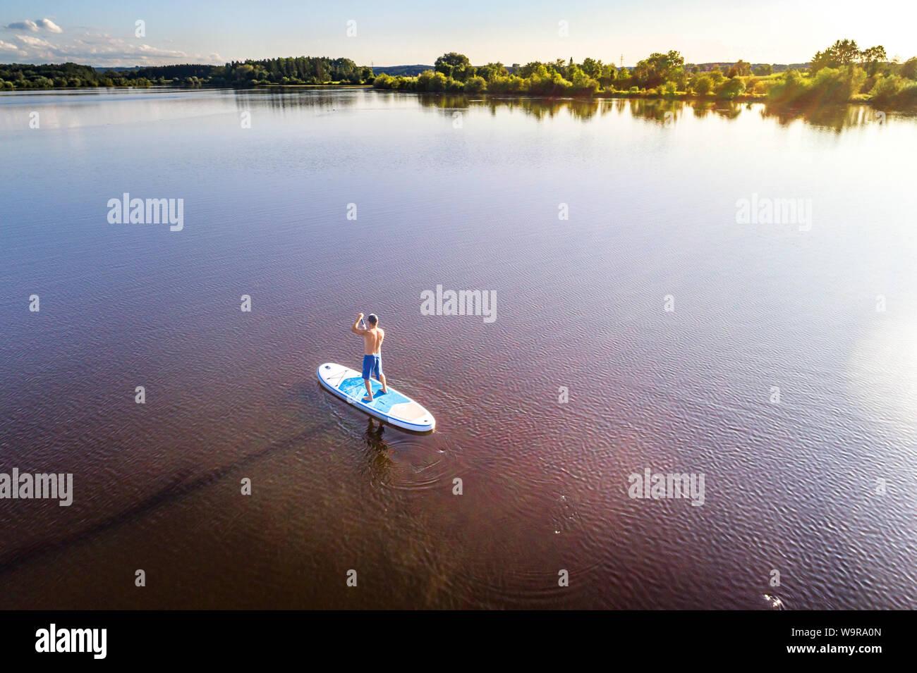 Alemania, Baviera, Allgaeu, standup Frankenhofner paddler en el lago al atardecer Foto de stock