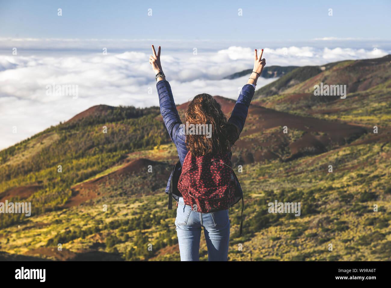 Adolescente con mochila y manos levantadas de pie en la cima de la montaña, con magníficas vistas al mar y bosque de nubes. Volcán Teide, Tenerife, España. Ad Foto de stock