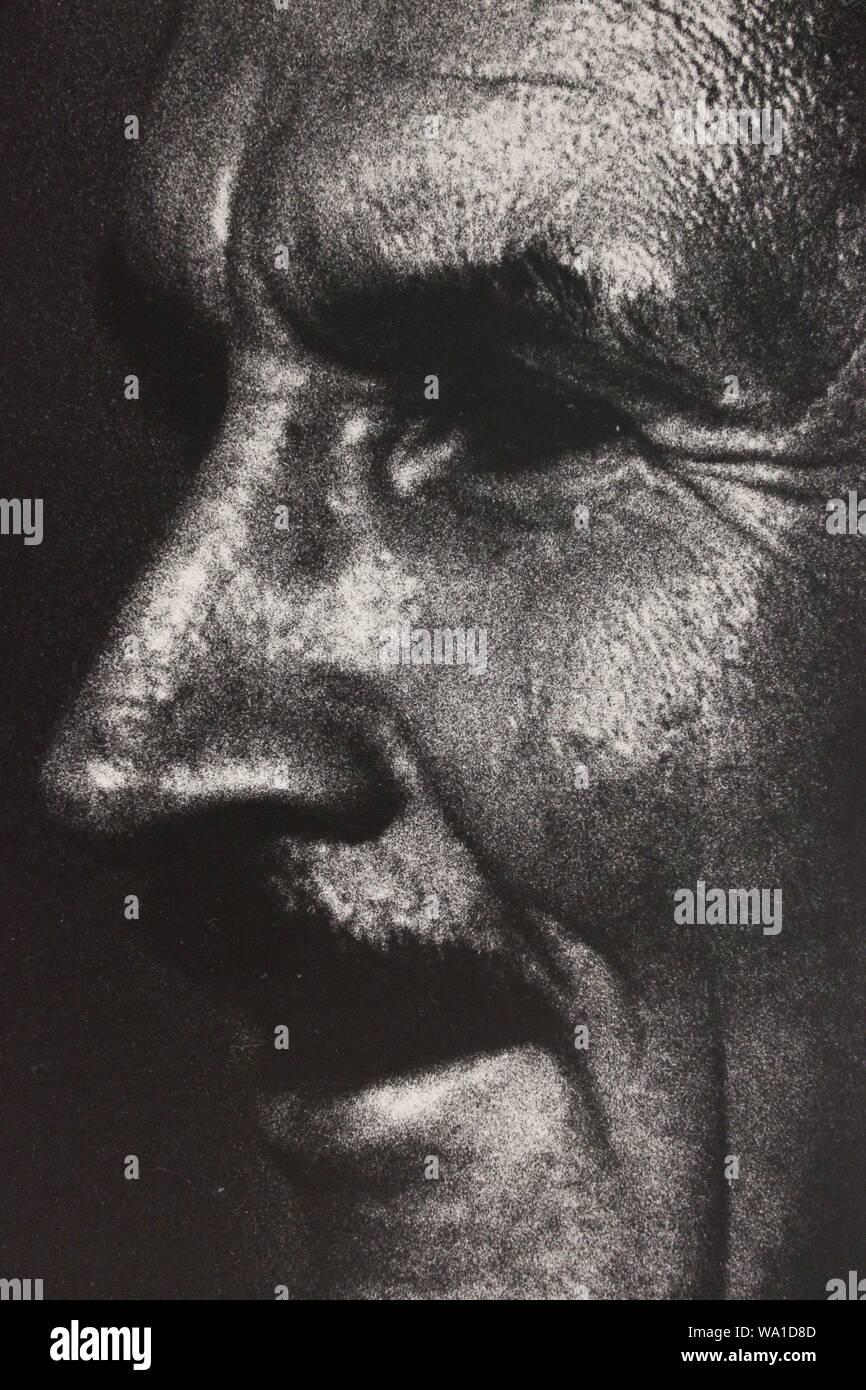 Fino arte fotografía en blanco y negro a partir de la década de 1970 de un hombre sospechoso de lo que está viendo. Foto de stock