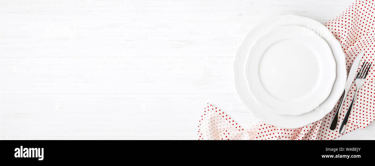 Platos y cubiertos vacía en blanco en polka dot servilleta en mesa de madera blanca. Vista superior de la tabla de configuración. Banner para web. Foto de stock