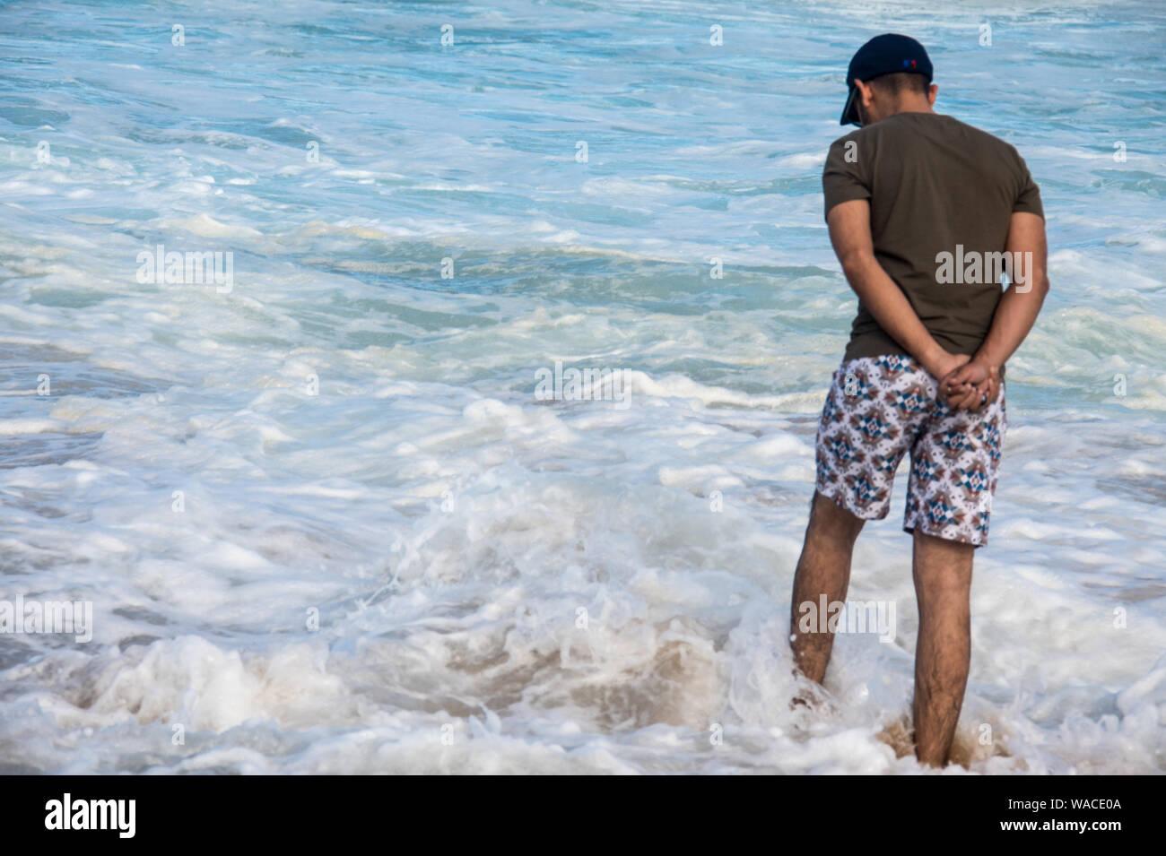 Un hombre en trajes de baño pensively casual de pie en el océano con las manos detrás de su espalda mientras mirando hacia abajo en una profunda reflexión. Las olas salpicando sobre él Foto de stock