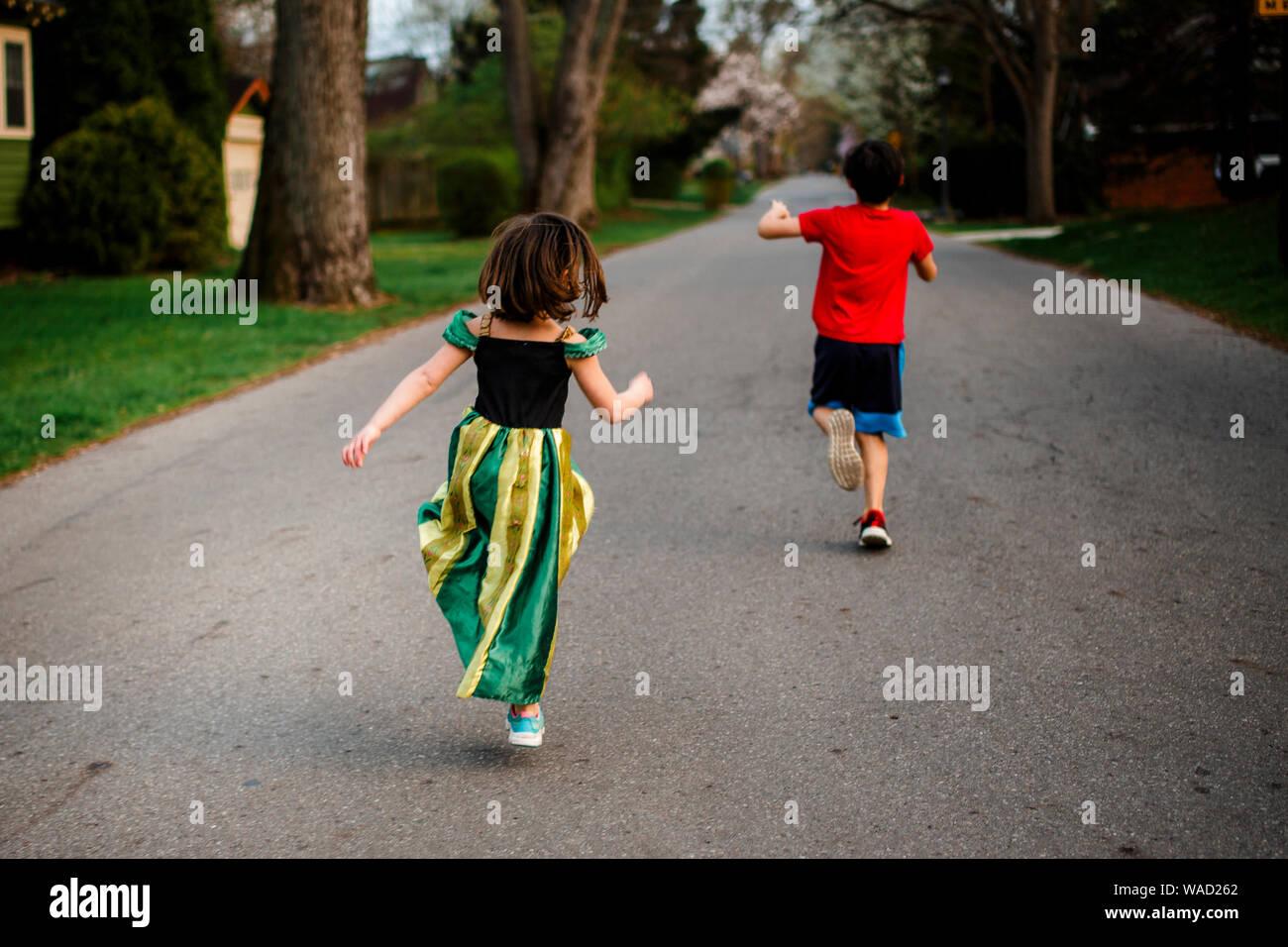 Dos niños saltar alegremente hacia abajo en una calle bordeada de árboles en primavera Foto de stock