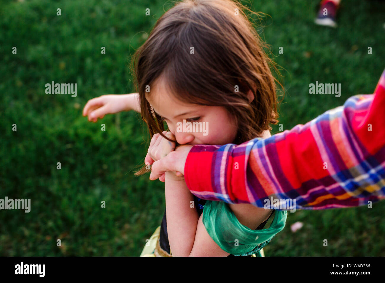 Vista anterior de una dulce niña sosteniendo la mano del padre y besarse es Foto de stock
