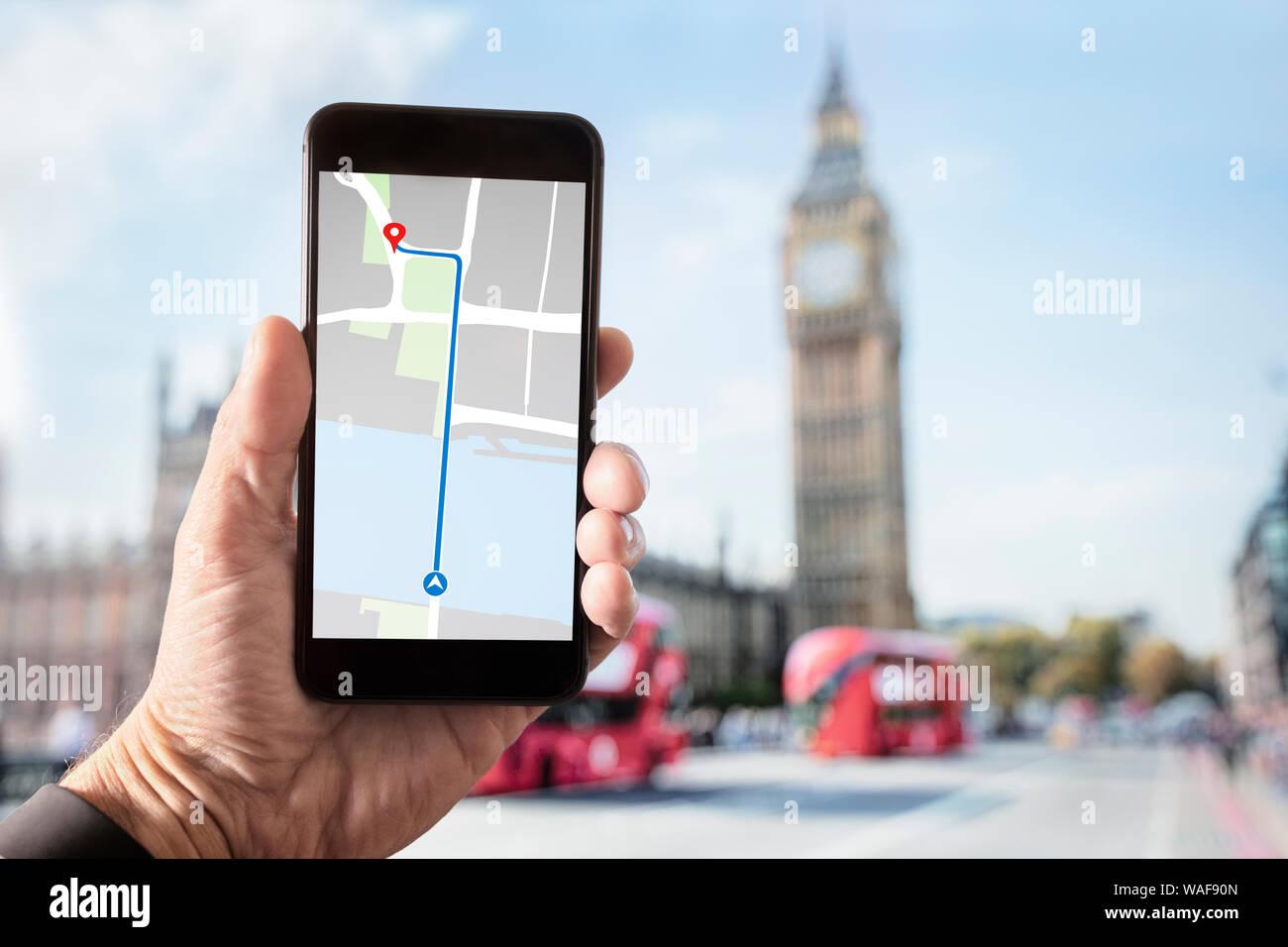 Mano sujetando con el mapa en la pantalla del smartphone en Londres frente al Big Ben y las Casas del Parlamento de Westminster Bridge Foto de stock