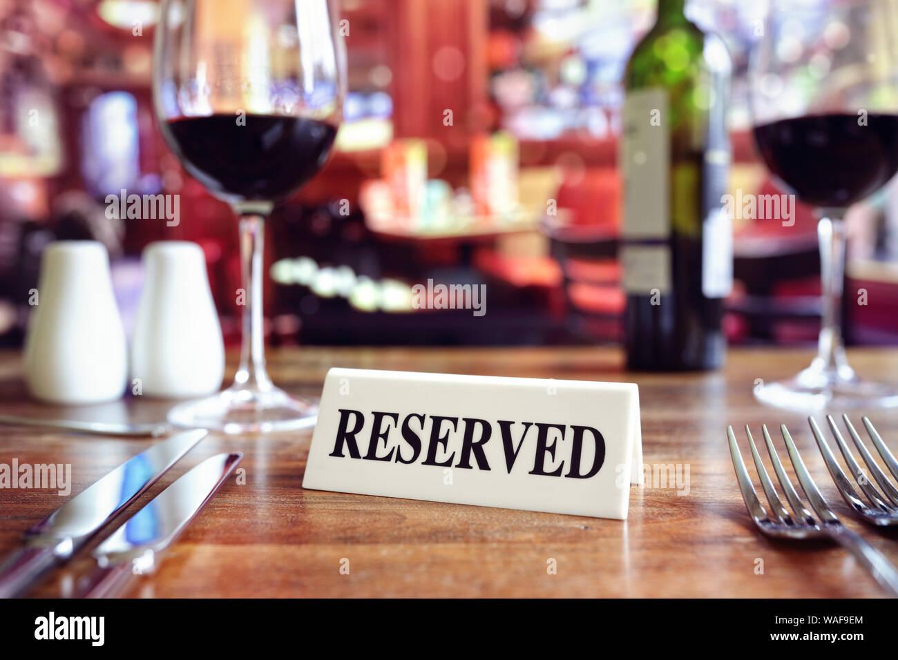 Restaurante reservado mesa firmar con lugares y copas de vino listo para una fiesta Foto de stock