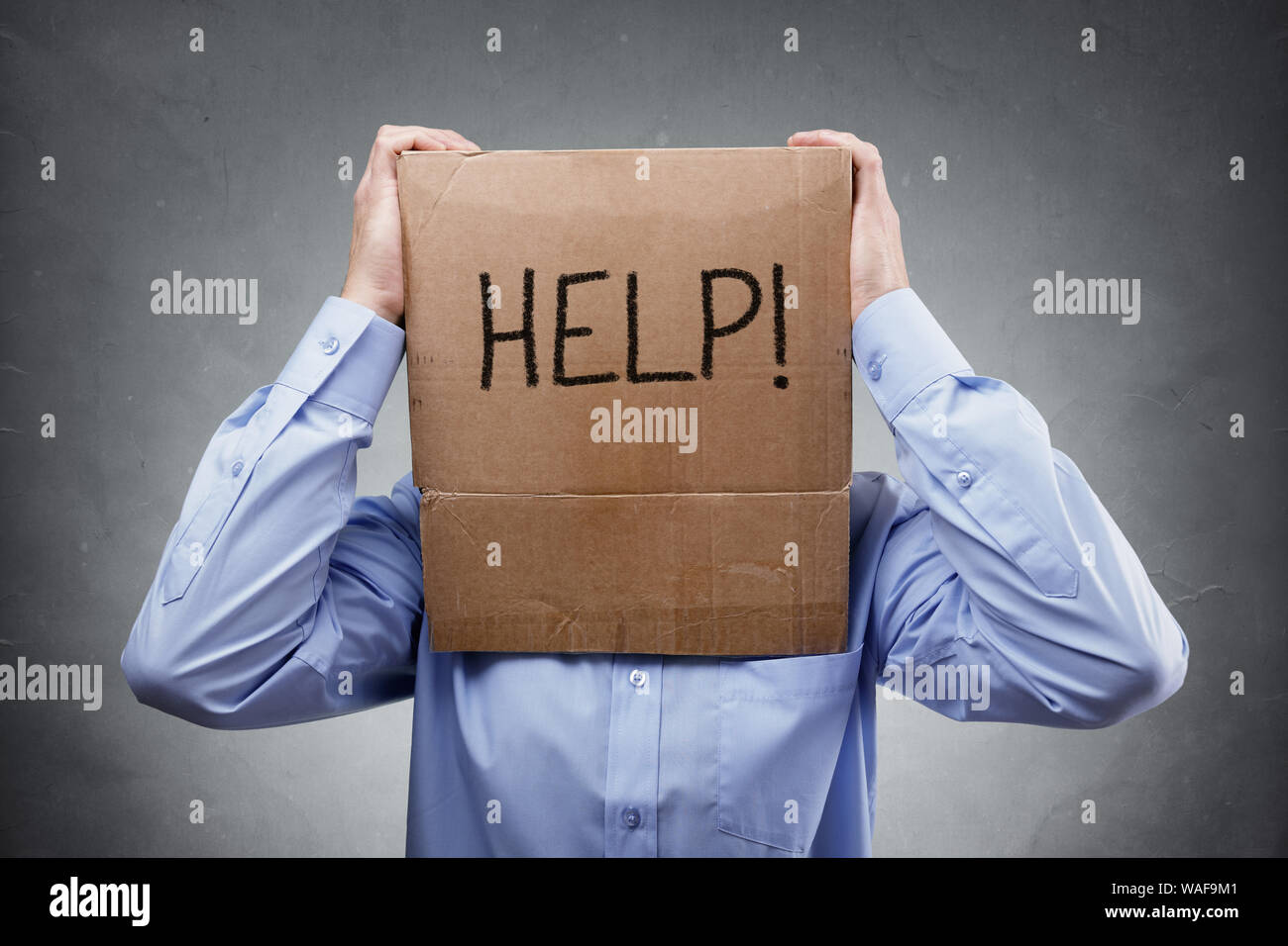 Caja de cartón en la cabeza empresario concepto pide ayuda para problemas, apoyo, sobrecargado de trabajo o estrés Foto de stock