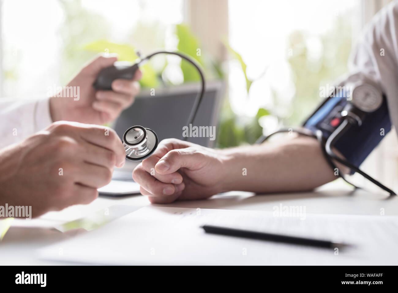 Médico controlar la presión sanguínea de un paciente Foto de stock