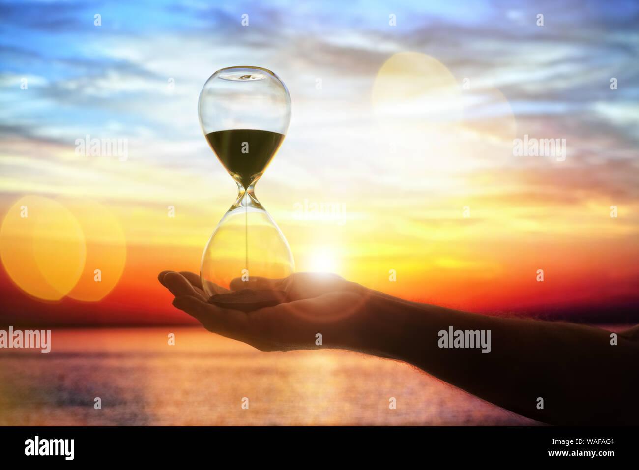 Tiempo de reloj de arena al atardecer fondo con espacio de copia Foto de stock
