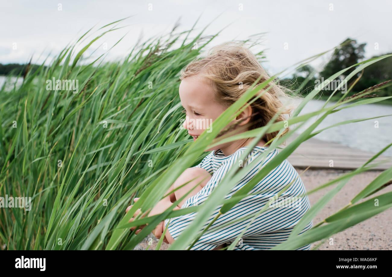 Retrato de una joven muchacha sentada sonriente en la playa en verano Foto de stock