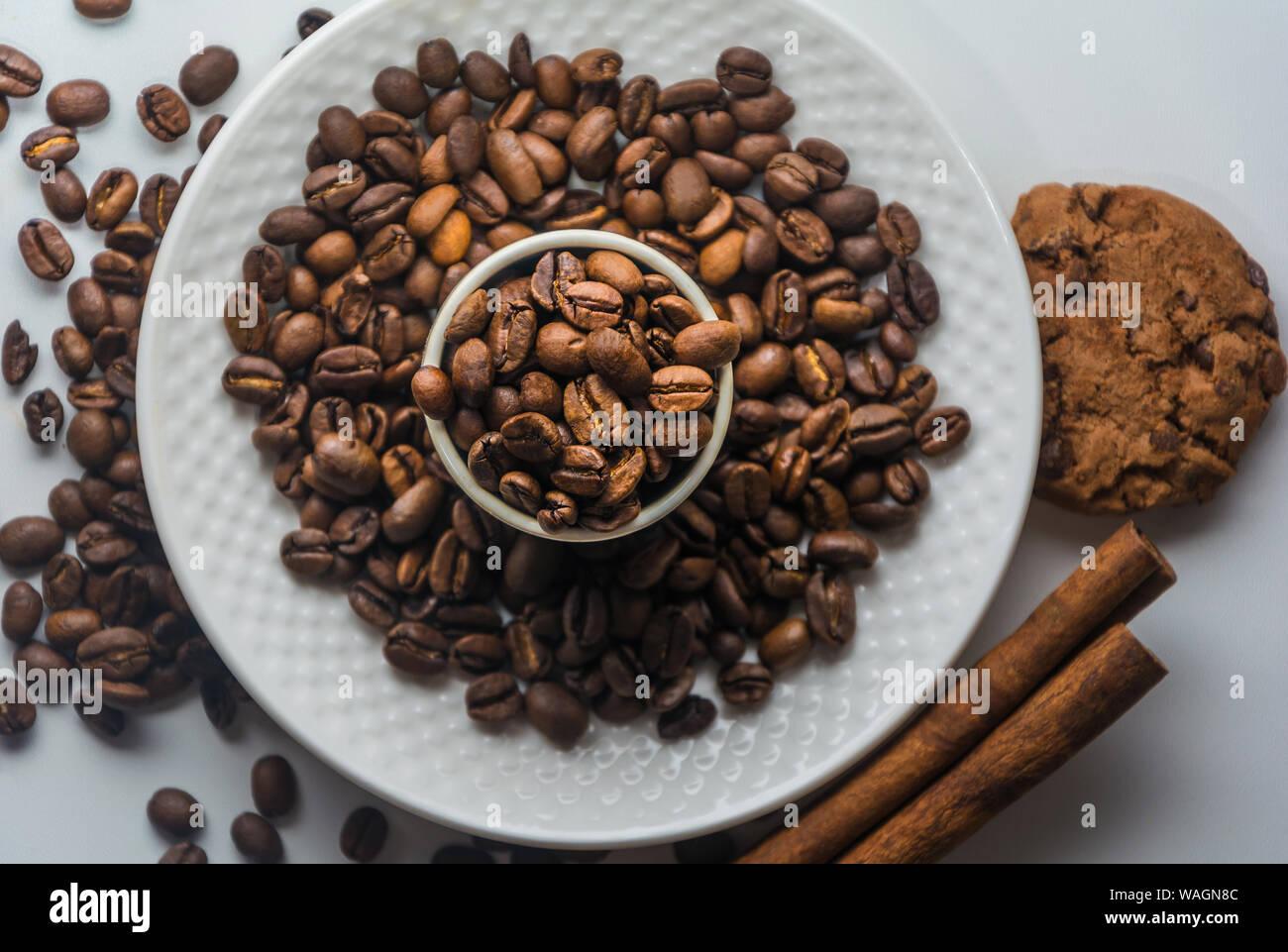 El blanco de la taza de café con café tostado en grano, canela y galletas sobre fondo blanco aisladas desde arriba. Los granos de café en la placa y en la taza. Foto de stock