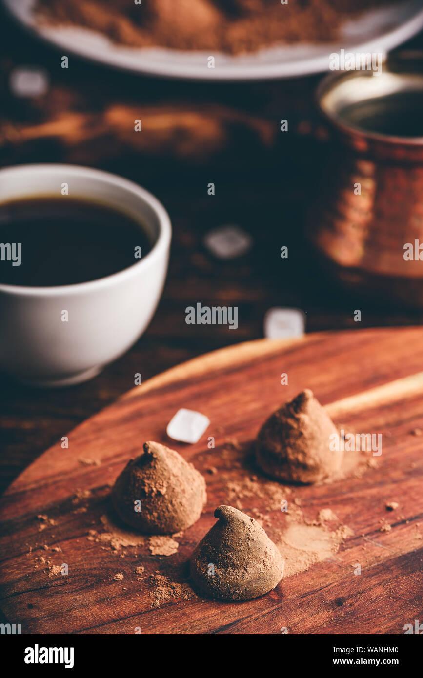 Trufas de chocolate caseras recubiertos de cacao en polvo con café negro Foto de stock