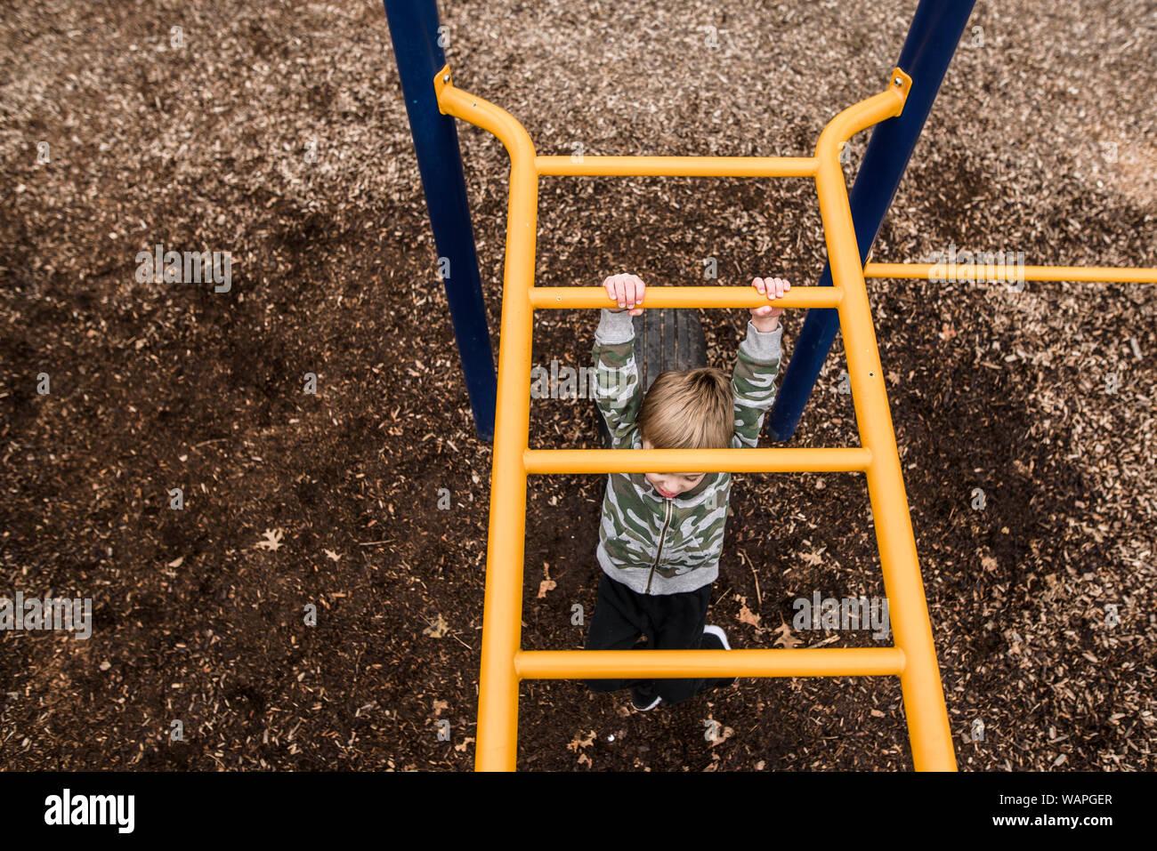 Mirando de arriba abajo al joven cruzando monkey bares en park Foto de stock