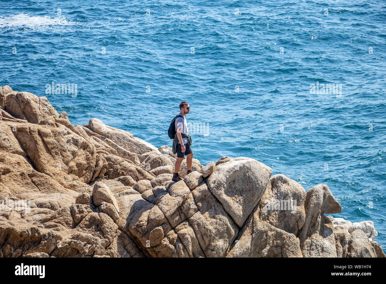Joven valiente caminante de pie en la rocosa costa del Océano Pacífico Foto de stock