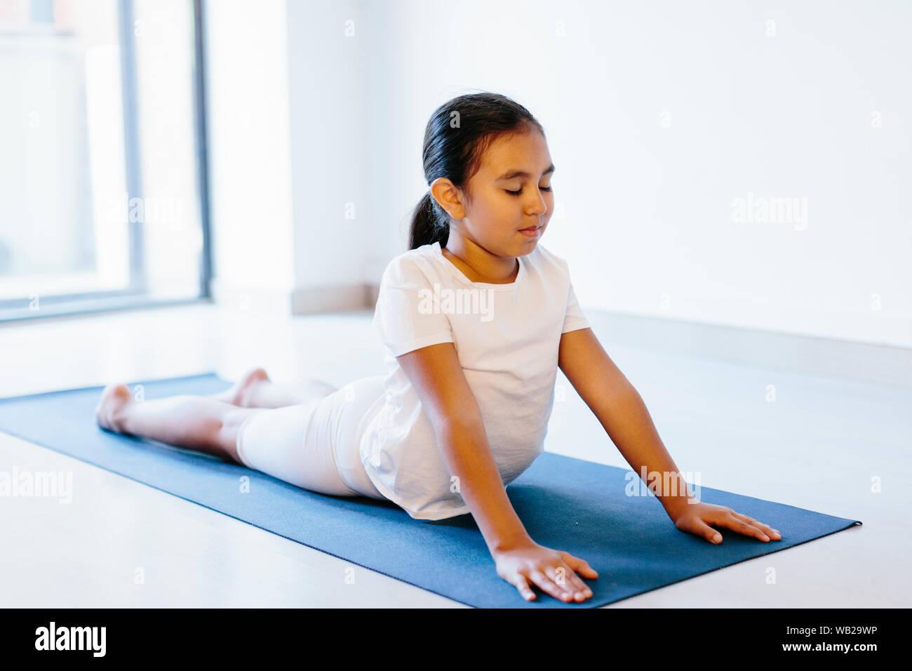 Una niña de 9 años es hacer yoga plantean acostado sobre una estera del yoga. Ella llevaba ropa blanca. Ella tiene características de etnia hispana. Foto de stock