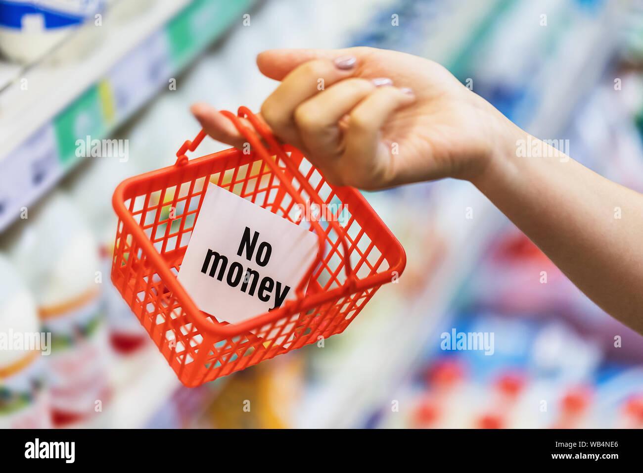 Una pequeña cesta de compras vacía en la mano. Concepto sobre la falta de dinero en efectivo para la compra de alimentos. No hay dinero pero te espera en Foto de stock